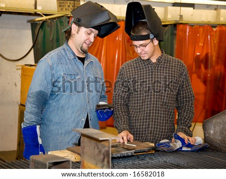 Two welders in a factory discussing how to work a piece of metal.  Authentic and accurate content depiction with all work being performed in accordance with industry code and safety regulations. - stock photo