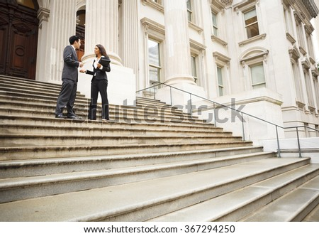 Two well dressed professionals in discussion on the exterior steps of a building. Could be lawyers, business people etc.