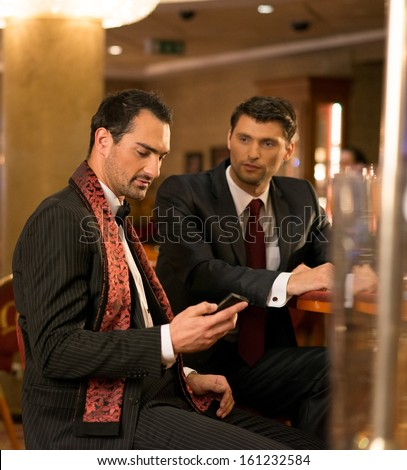 Two well-dressed young men with mobile phone behind table in luxury interior - stock photo