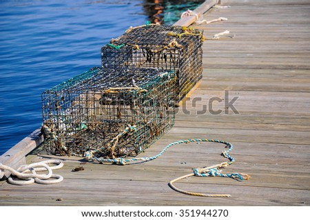 Two well used lobster pots sitting on a dock; A pair of heavily used lobster pots on a wooden dock waiting to be used - stock photo