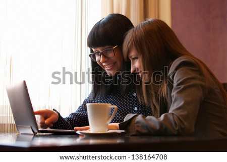 two wemen in cafe using laptop - stock photo