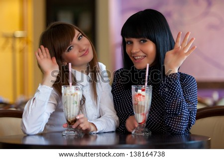 two wemen sitting in cafe and wave hand - stock photo