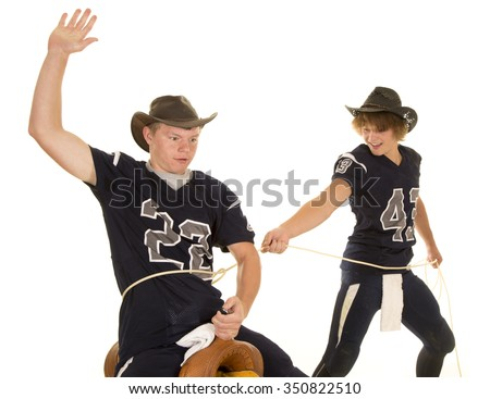 Two western football players, one it roping the other on the saddle - stock photo
