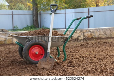 Two-wheeled wheelbarrow loaded with loose soil and a square-point spade on the cultivated area in the autumn garden under reconstruction