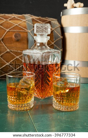 Two Whiskey Glasses And A Decanter On A Green Table Top, Against A  Background Of
