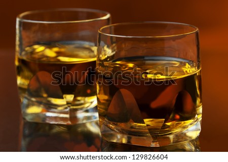 two whiskey glasses at warm backdrop - stock photo