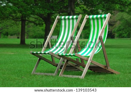 Two white and green chairs in the park