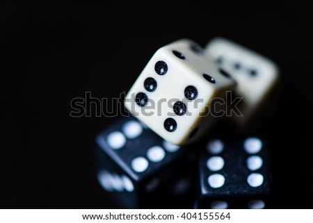 Two White and tro black Dices Isolated on Black Background