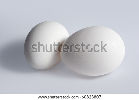 Two white chicken eggs on white background
