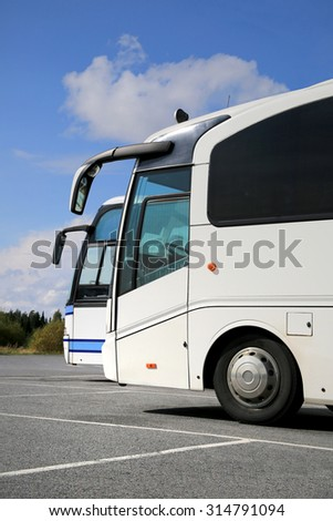 Two white coach buses on parking lot at summer with blue sky and some clouds, vertical view. - stock photo