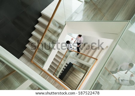 Two white-collars discussing something standing on the staircase - stock photo