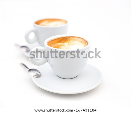 Two white cups of Cappuccino coffee with heart shaped milk foam - stock photo