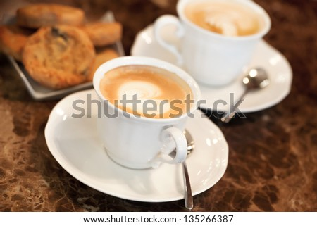 Two white cups of Cappuccino coffee with heart shaped milk foam. Selective focus