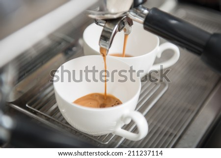 Two white cups standing on the grating of coffee machine and coffee pouring into them - stock photo