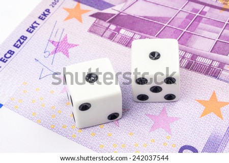 Two white dices with black dots are laying on 500 euro banknote - stock photo