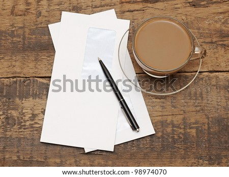 two white envelopes with black pen on wood background - stock photo
