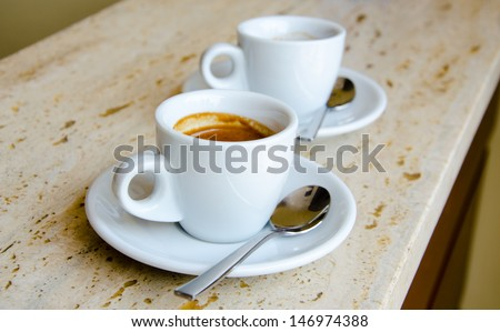 Two white espresso cups standing on the marble table