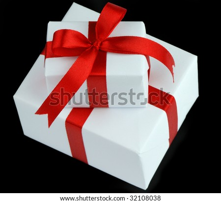 two white gift boxes with red ribbon isolated on black background