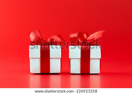 Two white gift boxes with ribbons on red background - stock photo