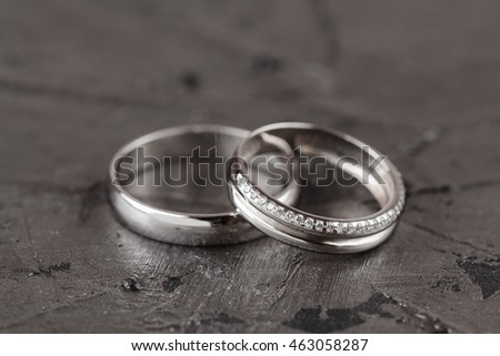 Two white golden wedding rings on black background. Bride ring with diamonds. Shallow focus