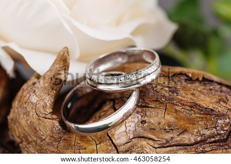 Two white golden wedding rings on wood background. Bride ring with diamonds. Shallow focus. Rustic concept