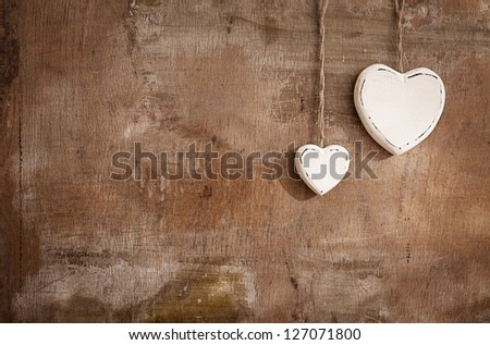 two white hearts made of wood in different sizes on grunge background - stock photo