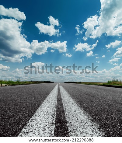 two white lines on black road and dramatic sky with clouds over it - stock photo