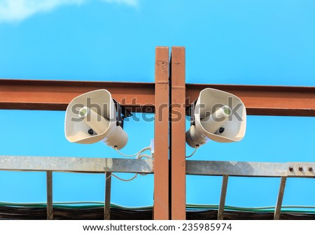 Two white loudspeakers on the brown metal construction - stock photo