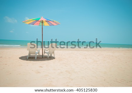 Two white lounge chairs with colorful sun umbrella on a beach
