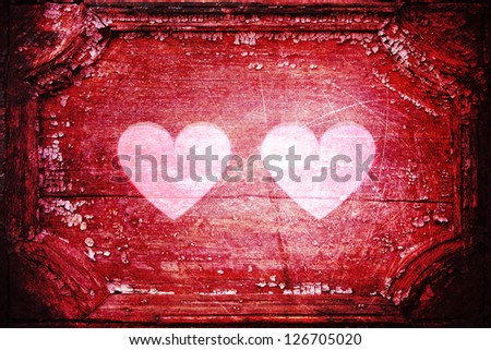 Two white, luminous hearts inside an old red wooden frame. Vivid red color with dark edges. Aged rough background. - stock photo