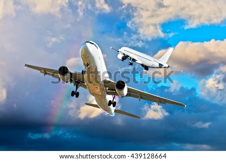 Two white passenger airplanes are climb very close in a cloudy sky. Aircraft are flying against the background of the rainbow. - stock photo