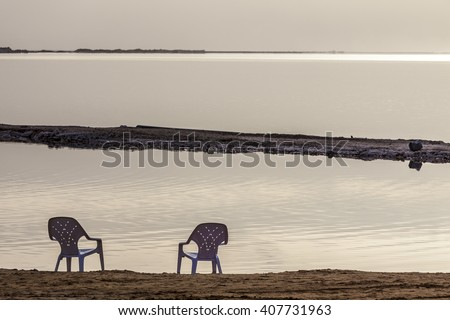 Two white plastic chairs at lonely beach in the early morning