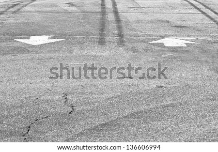 Two white road arrows. Textured grey asphalt, painted road markings of 2 arrows pointing in opposite directions in a parking lot with dirty and cracked pavement. - stock photo