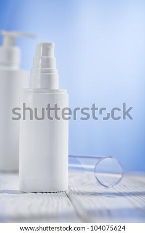 two white skincare sprayres on wooden table - stock photo