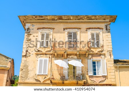 Two white sun umbrellas on balcony of a typical old house in Erbalunga town, Corsica island, France - stock photo