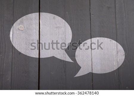 Two white text balloons on dark black wooden background - stock photo