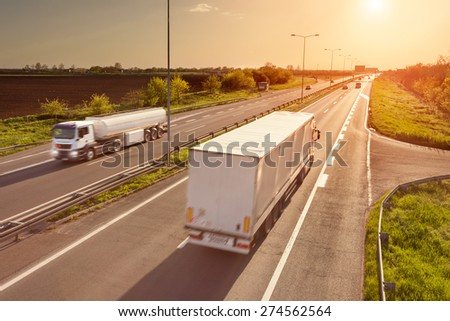Two white trucks in motion blur on the freeway towards the setting sun. Rush hour on the motorway near Belgrade - Serbia. - stock photo