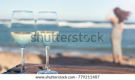 Two white wine wineglasses over sea background.Tropical vacation on beach.
