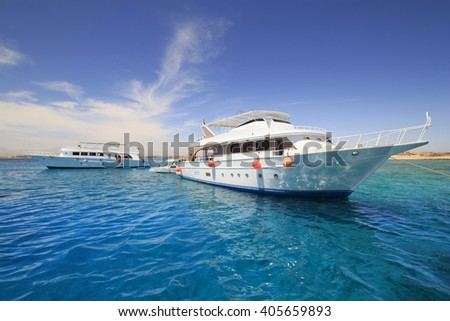 Two white yachts in open sea with clean blue water