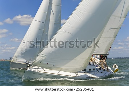 Two white yachts racing close to each other on a bright sunny day