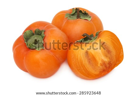 Two whole and a half of ripe persimmon with green leaves isolated on white background