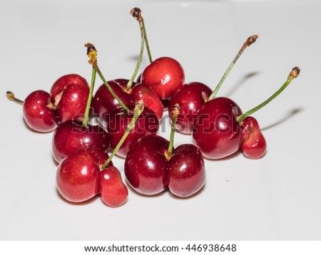 Two whole cherries joined like Siamese twins and sharing a single stem