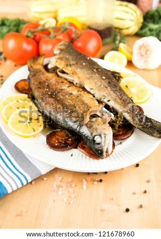 Two Whole Rainbow Trouts Fried and Served with Vegetables - stock photo