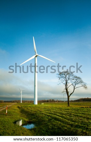 Two wind electric generators in field - stock photo