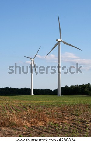 Two wind power generators in a field shot against a blue sky.