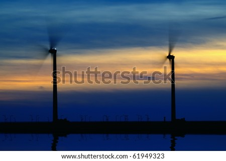 two wind-turbines at seacoast in sunset