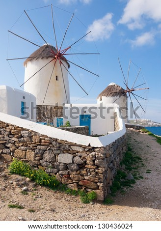 Two windmills of Mykonos. White buildings, blue sky and the sea - the national colors of Greece - stock photo