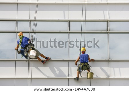 Two window cleaners in the building - stock photo