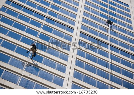 Two windows cleaners hanging on safety rope