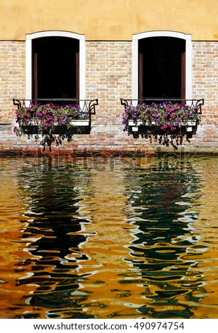 Two windows on an ancient building in Venice, with baskets of colorful flowers, reflecting in the water of the Venetian channel, Venice, Italy